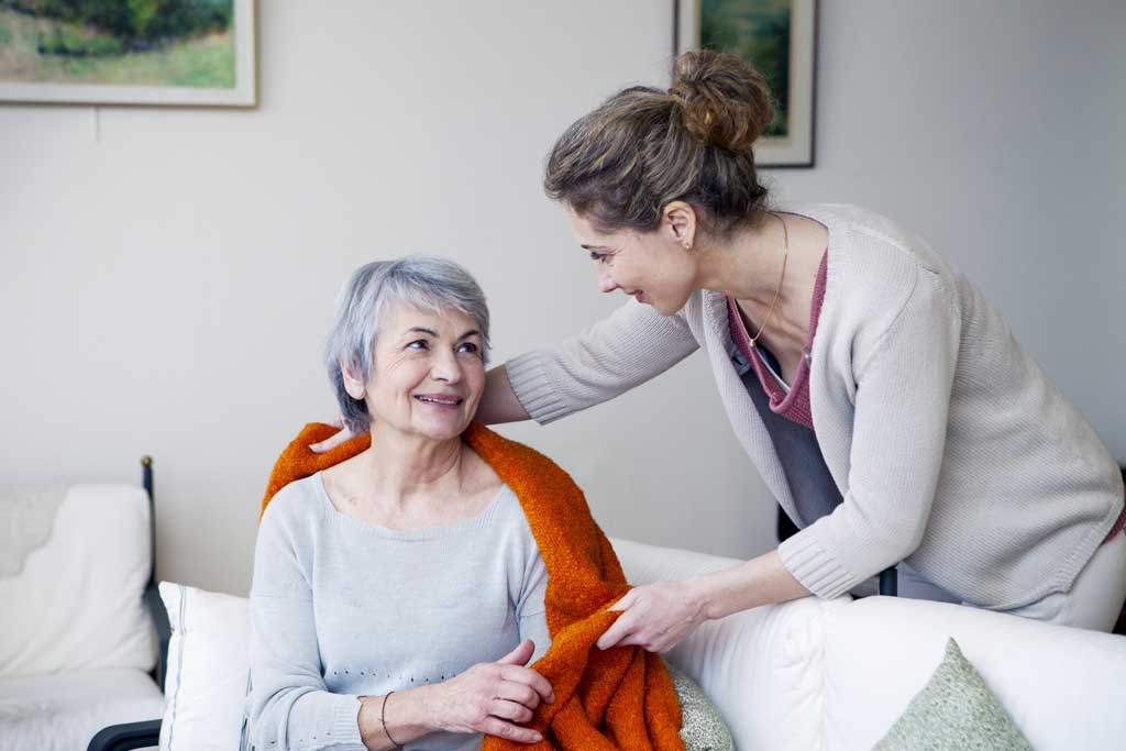 Senior citizen getting help from woman
