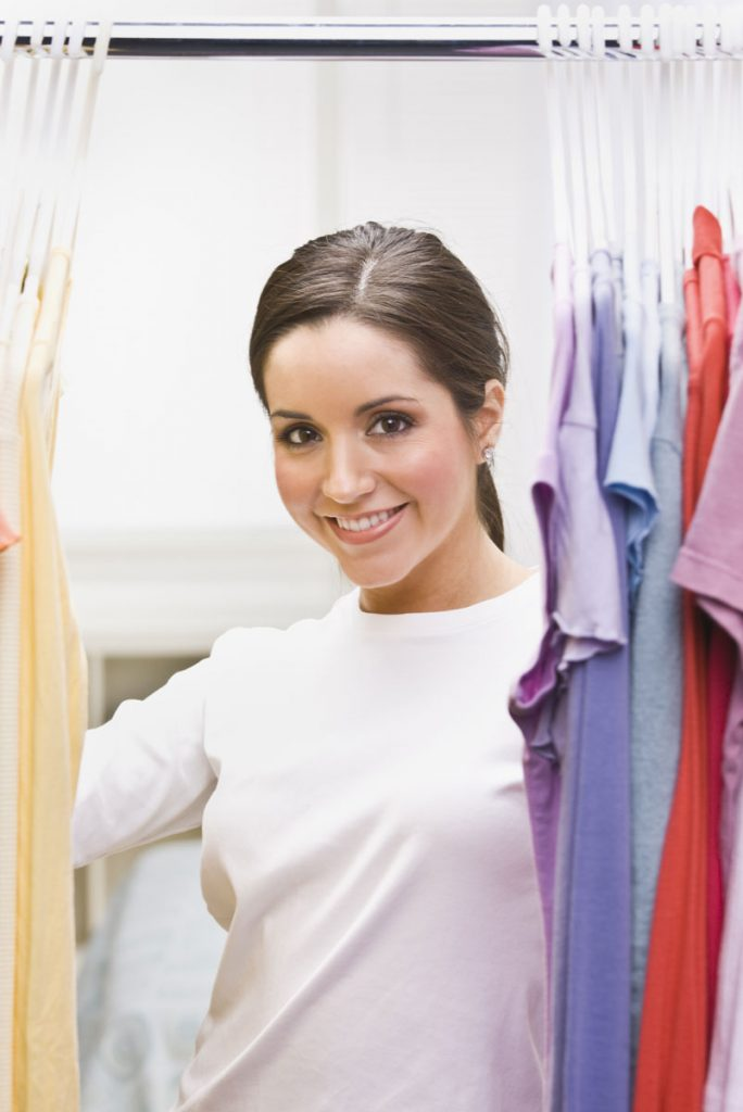 woman in closet with shirts